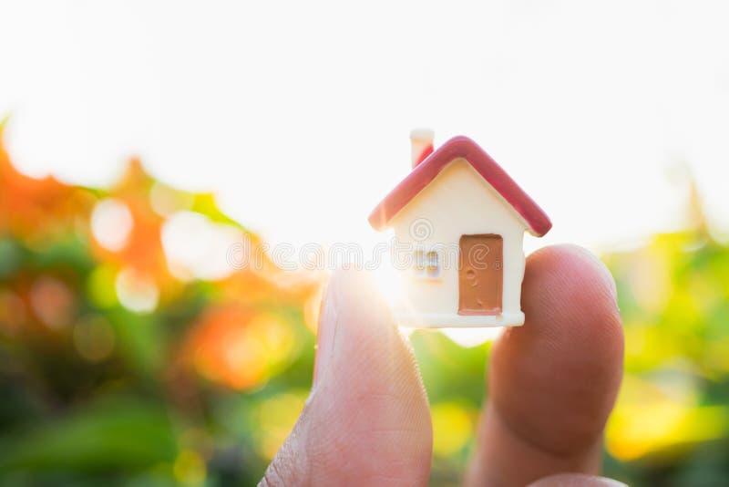 Mano che tiene casa miniatura usando come concetto della proprietà fotografie stock libere da diritti