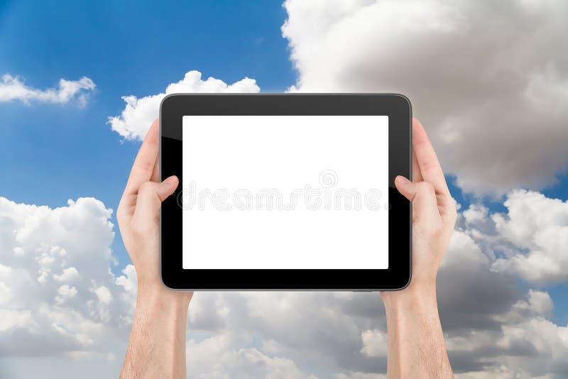 Mano che tiene compressa in bianco su nuvoloso immagini stock libere da diritti