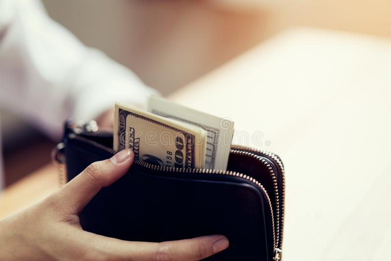 Mano che tiene 100 dollari di fatture in portafoglio Il concetto della spesa dai contanti fotografie stock