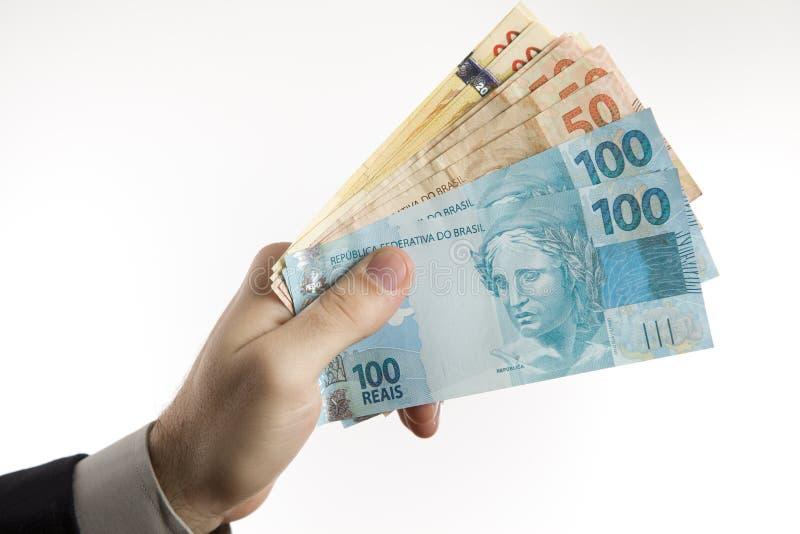 Mano che tiene i soldi brasiliani immagini stock