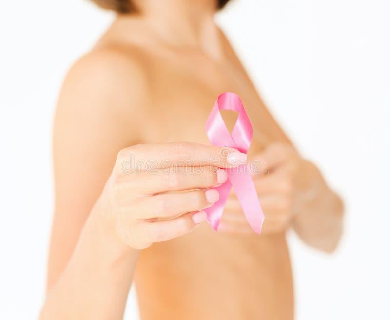 Mano che tiene il nastro rosa di consapevolezza del cancro al seno fotografie stock libere da diritti