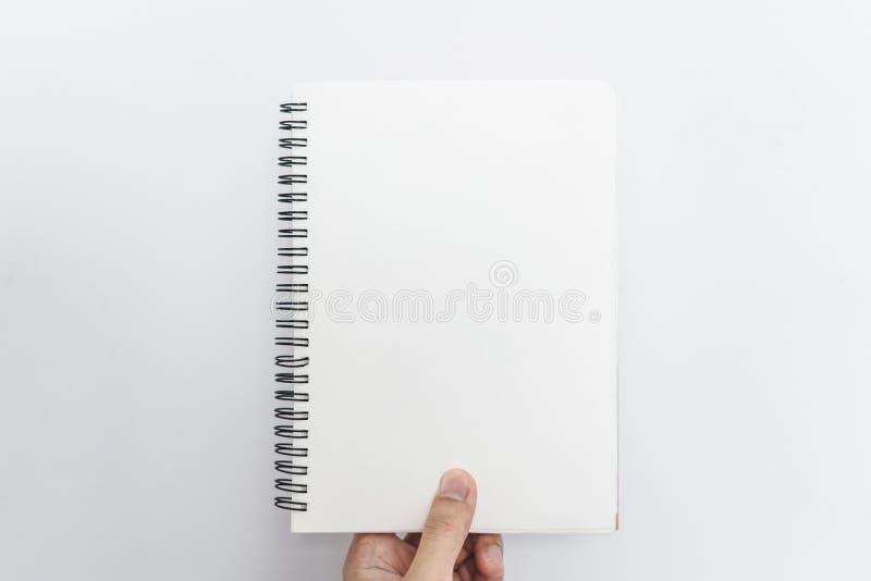 Mano che tiene il taccuino aperto dei paraocchi, pagine vuote in bianco, su fondo bianco immagine stock