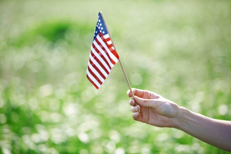 Mano che tiene la bandiera degli Stati Uniti per la festa dell'indipendenza fotografie stock libere da diritti