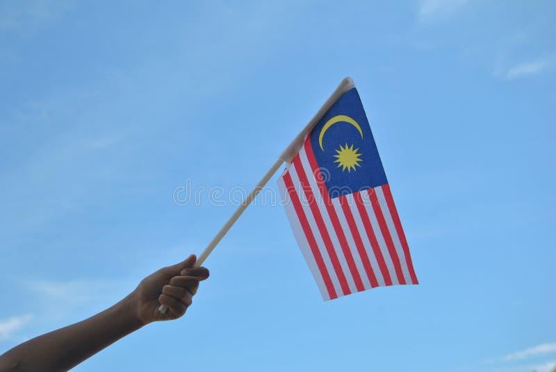 Mano che tiene la bandiera della Malesia fotografie stock libere da diritti