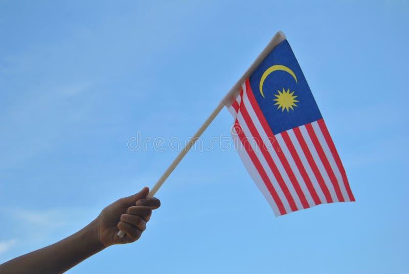 Mano che tiene la bandiera della Malesia fotografia stock