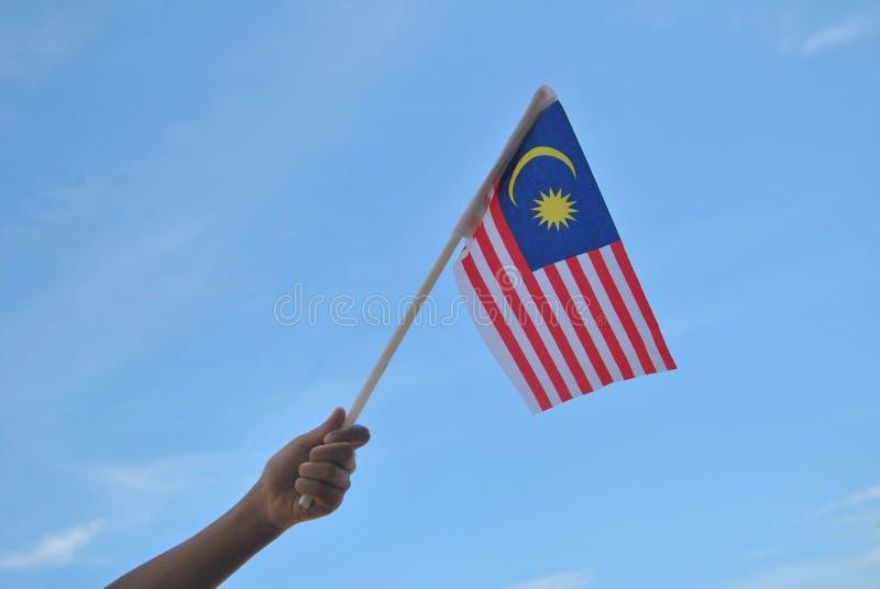 Mano che tiene la bandiera della Malesia immagini stock