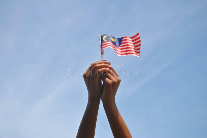 Mano che tiene la bandiera della Malesia immagini stock libere da diritti