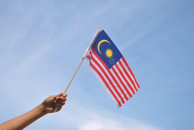 Mano che tiene la bandiera della Malesia immagine stock