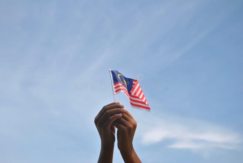 Mano che tiene la bandiera della Malesia immagine stock libera da diritti