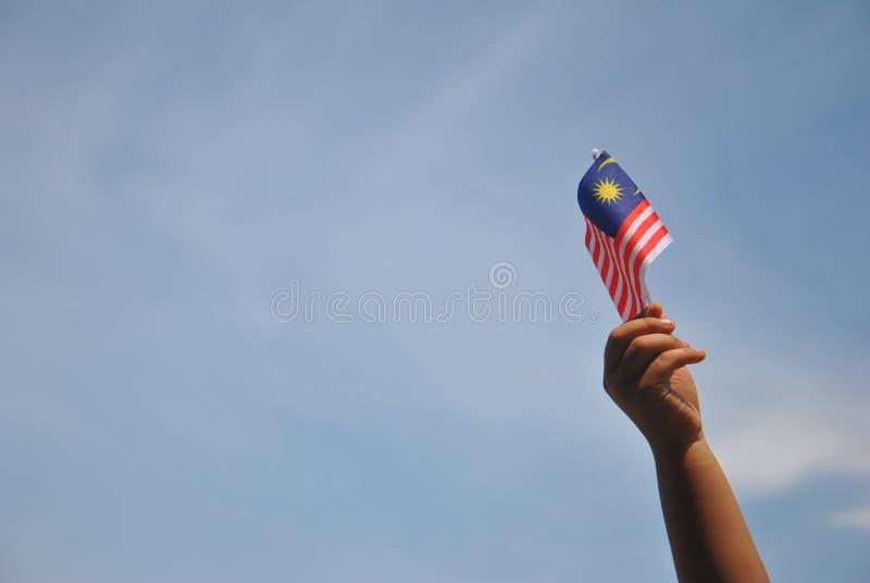 Mano che tiene la bandiera della Malesia fotografie stock