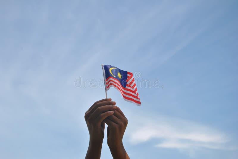 Mano che tiene la bandiera della Malesia fotografia stock libera da diritti