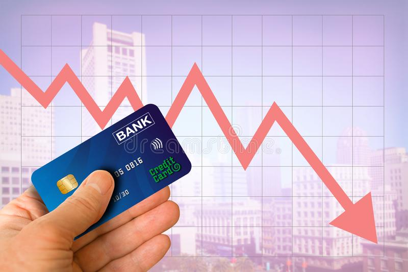 Mano che tiene la carta di credito dalla banca con paesaggio urbano e la freccia rossa che scendono l'economia del mercato immobi immagine stock