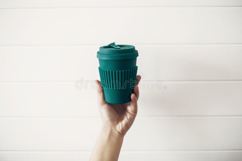 Mano che tiene la tazza di caffè riutilizzabile alla moda di eco su fondo di legno bianco Tazza verde da fibra di bambù naturale, fotografia stock