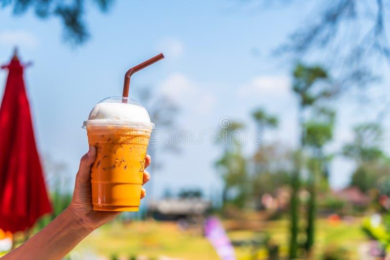 mano che tiene la tazza di tè tailandese ghiacciata del latte immagini stock