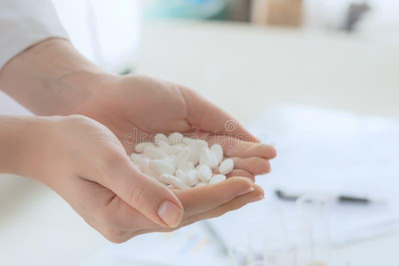 Mano che tiene le pillole bianche: concetto sano della medicina della farmacia fotografia stock libera da diritti
