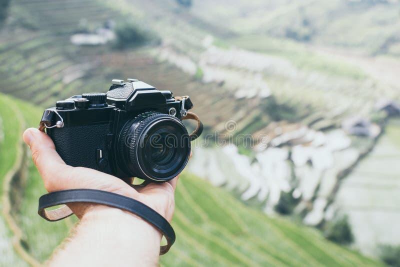 Mano che tiene macchina da presa d'annata con i terrazzi del riso di Sapa su fondo, Vietnam fotografia stock libera da diritti