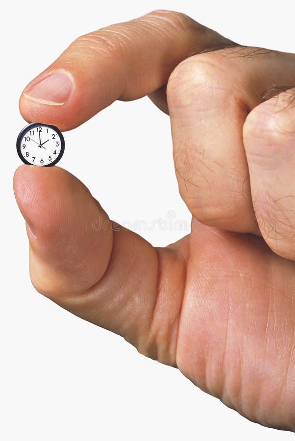 Mano che tiene orologio molto piccolo fotografia stock