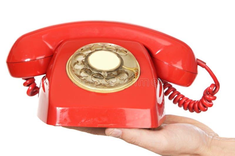 Mano che tiene telefono rosso fotografia stock