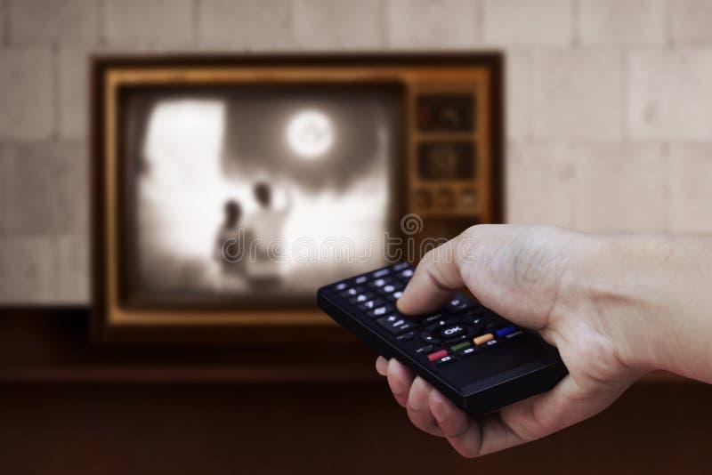 Mano che tiene TV a distanza fotografia stock libera da diritti