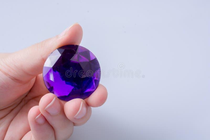 Mano che tiene un diamante porpora su fondo bianco immagine stock libera da diritti