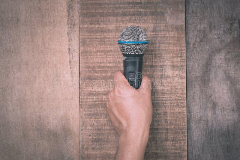 Mano che tiene un microfono su fondo di legno immagine stock