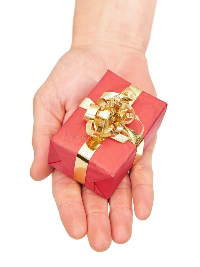 Mano che tiene un piccolo regalo di Natale immagini stock libere da diritti