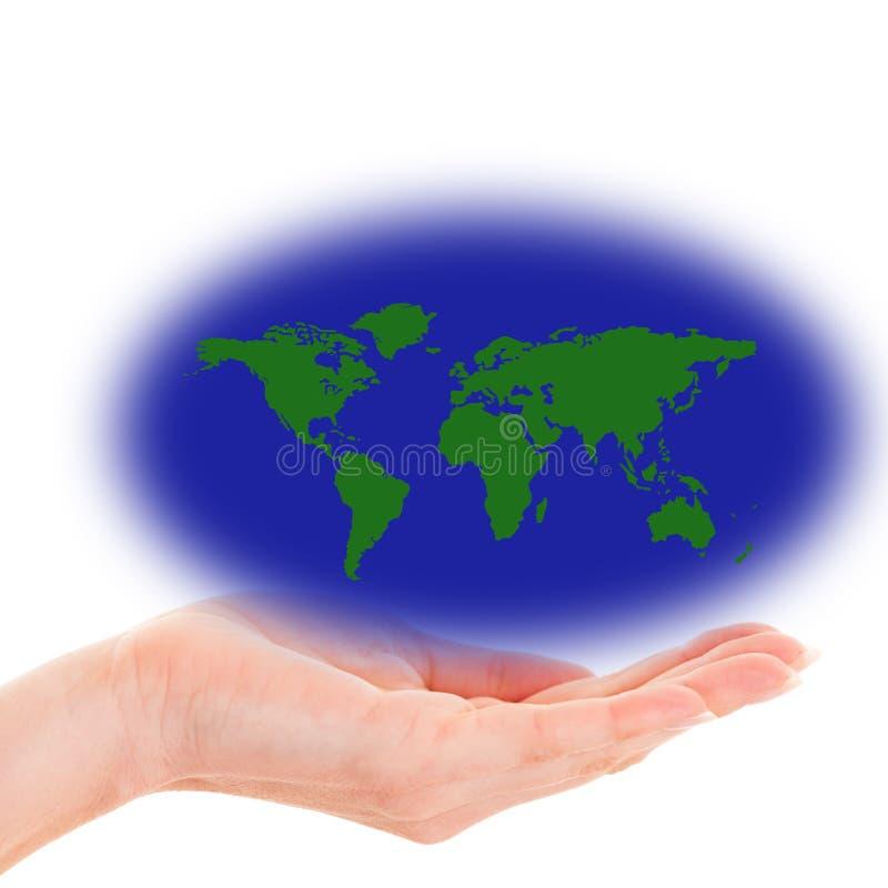 Mano che tiene una mappa di mondo con le masse verdi della terra fotografia stock