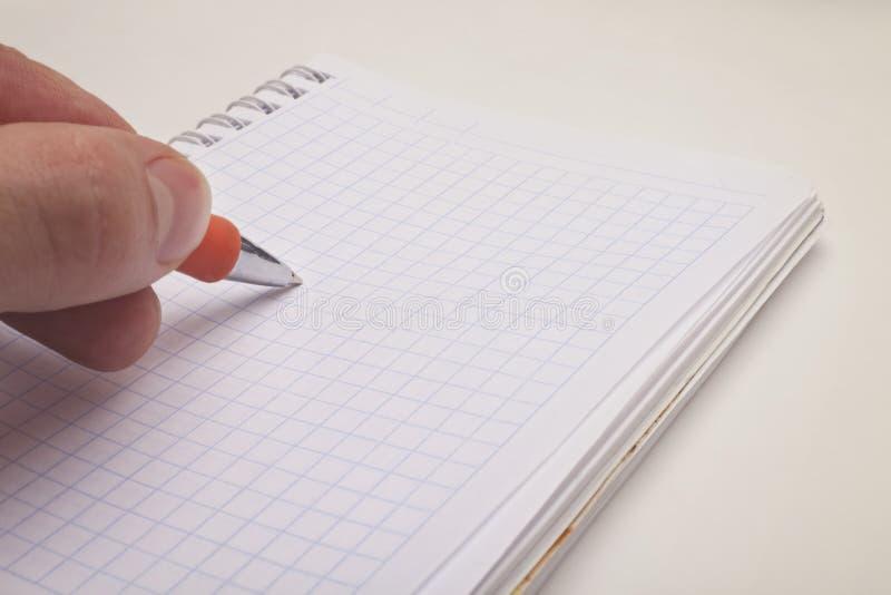 Mano che tiene una penna e un blocchetto per appunti di ballpoint immagini stock libere da diritti