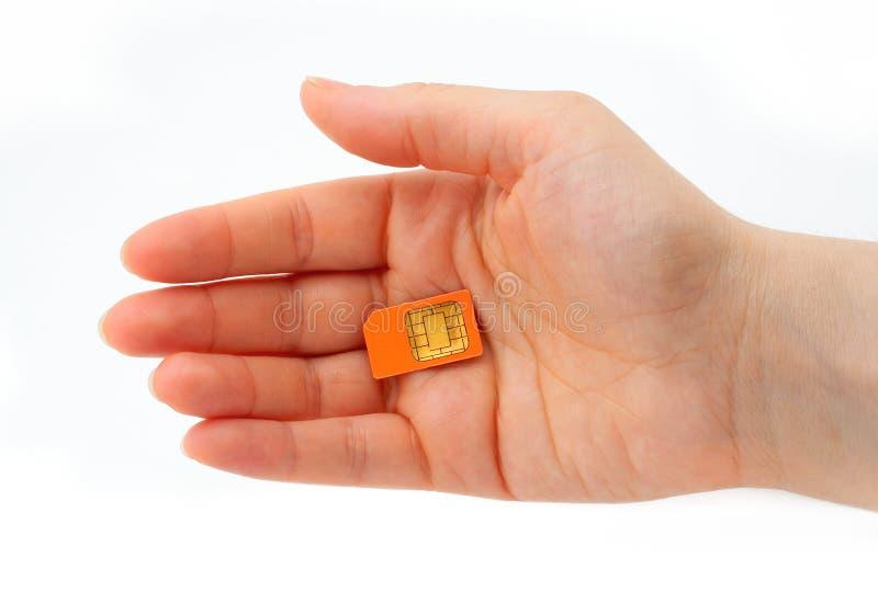 Mano che tiene una scheda di SIM fotografia stock libera da diritti