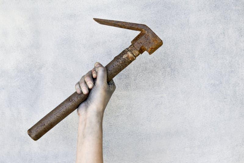 Mano che tiene vecchio martello arrugginito su fondo grigio immagine stock libera da diritti