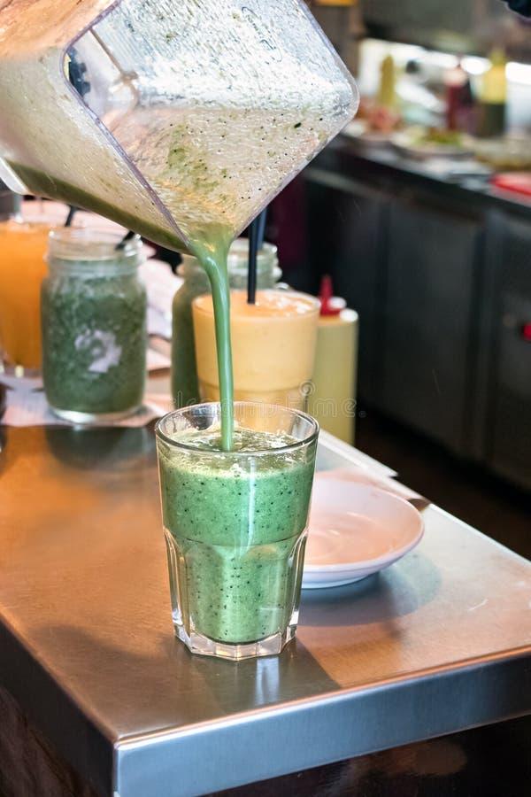 Mano che versa una forma smoothy di verdure della disintossicazione verde un miscelatore ad un vetro trasparente fotografie stock