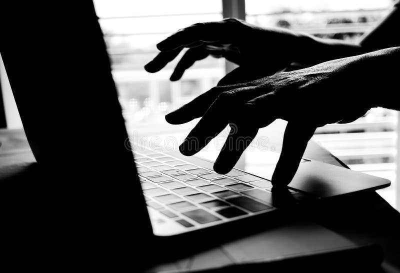 Mano cibernética del crimen que alcanza hacia fuera con el ordenador portátil y el ataque fotos de archivo libres de regalías