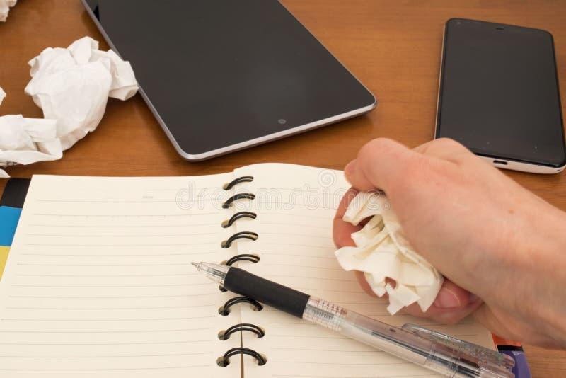 Mano con carta sgualcita, penna sul taccuino, cellulare immagine stock libera da diritti