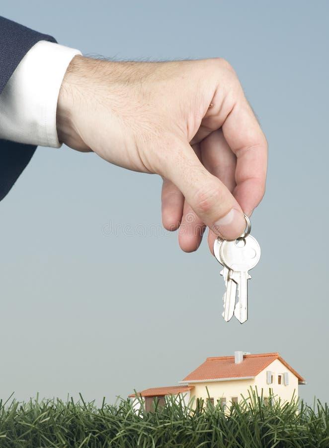 Mano con claves y una pequeña casa imagen de archivo libre de regalías