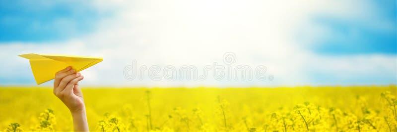Mano con el avión de papel amarillo El niño enciende un aeroplano de papel en el cielo, en luz de la mañana en verano al aire lib imagen de archivo libre de regalías