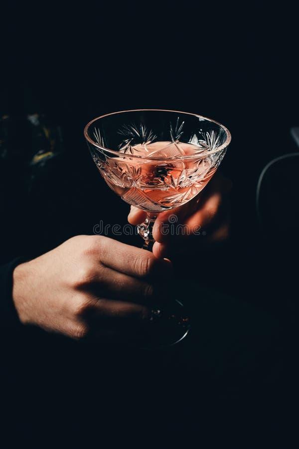 mano con el cóctel del alcohol que hace la tostada aislada en un fondo negro imagen de archivo libre de regalías
