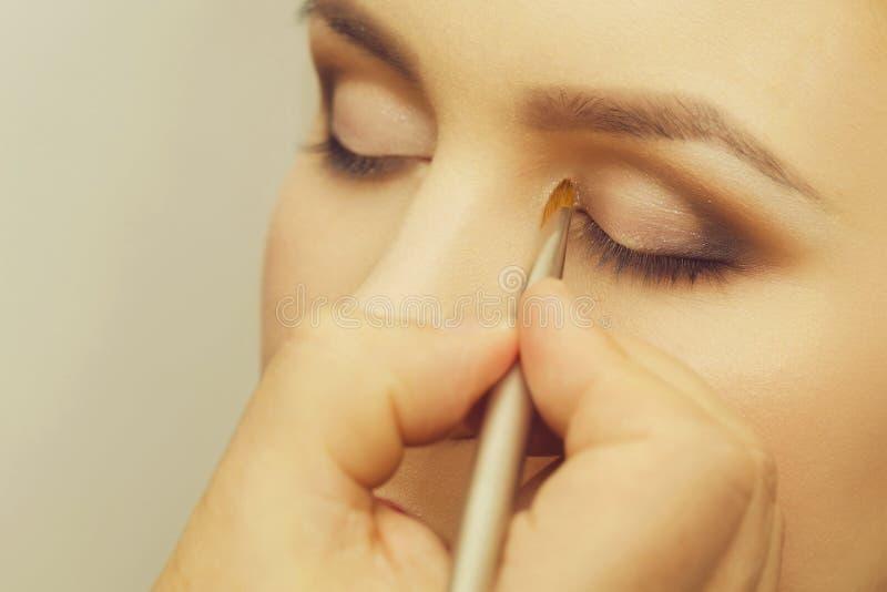 Mano con el cepillo que aplica sombras en cara de la mujer imágenes de archivo libres de regalías