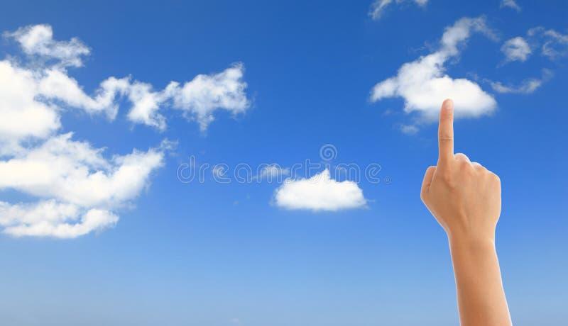 Mano con el cielo azul y la nube blanca imagen de archivo