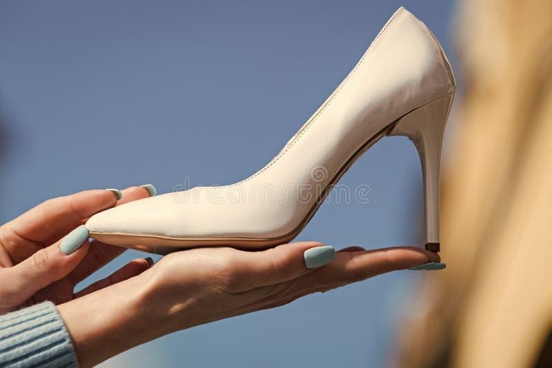 Mano con el cuero blanco del color del zapato femenino del encanto imagen de archivo libre de regalías
