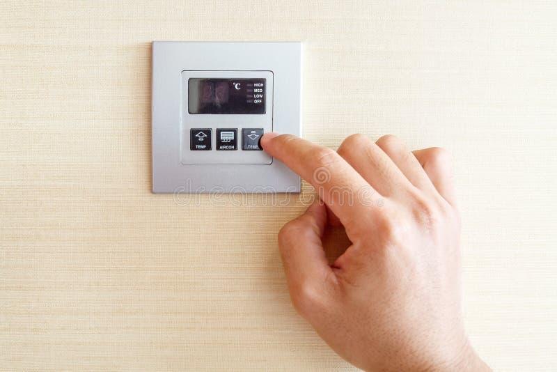 Mano con el dedo en control del interruptor del acondicionador de aire fotografía de archivo libre de regalías