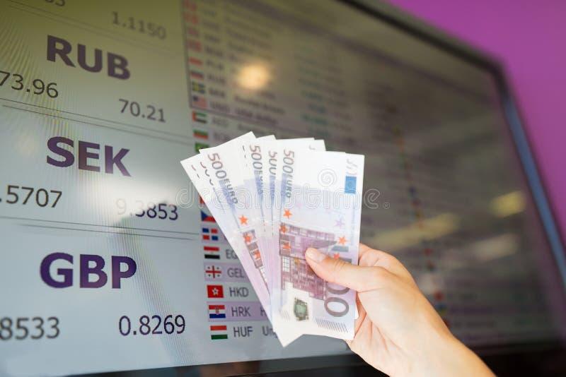 Mano con el dinero euro sobre los tipos de cambio de moneda imagenes de archivo