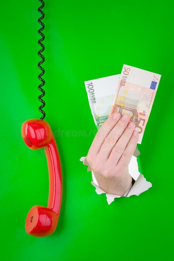 Mano con el dinero y el teléfono fotos de archivo