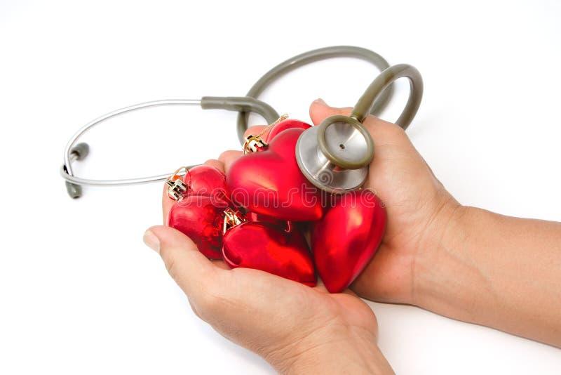 Mano con el estetoscopio que examina el corazón rojo imagen de archivo