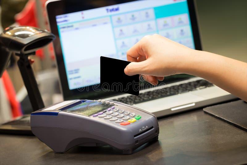 Mano con el golpe fuerte de la tarjeta de crédito a través del terminal para la venta fotografía de archivo
