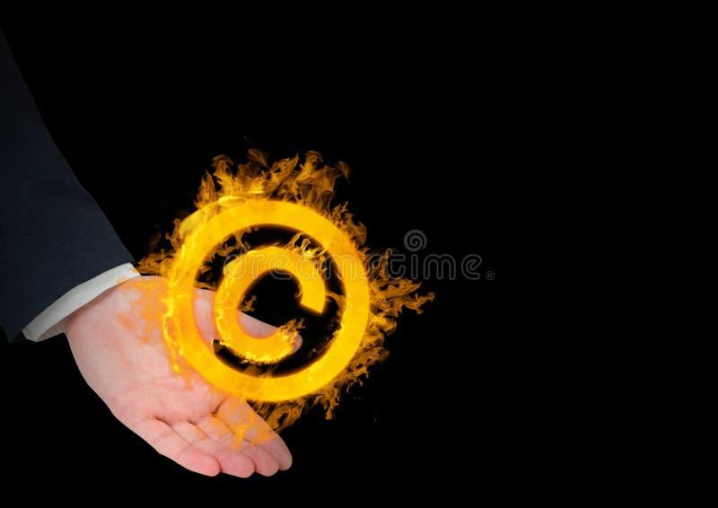 mano con el icono del fuego del copyrighht encima Fondo negro foto de archivo