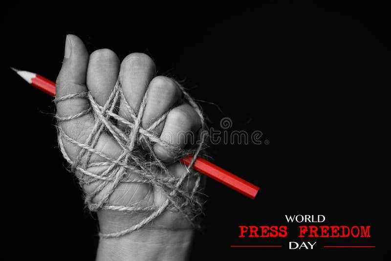 Mano con el lápiz rojo atado con la cuerda imagen de archivo