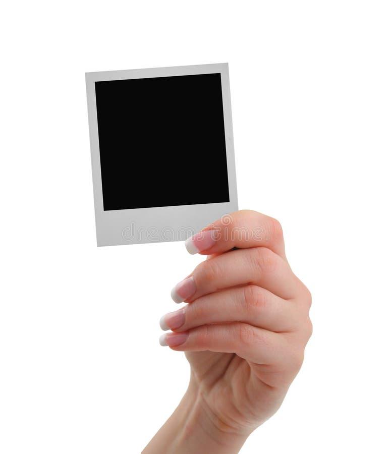 Mano con el marco polaroid foto de archivo libre de regalías