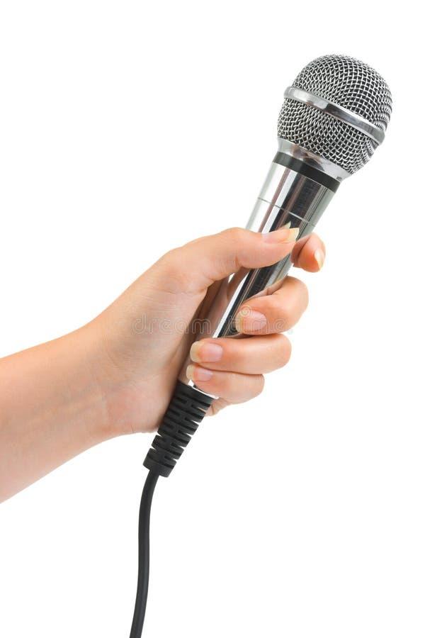 Mano con el micrófono imagen de archivo