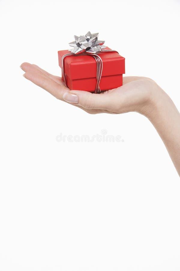 Mano con el pequeño regalo envuelto fotografía de archivo libre de regalías
