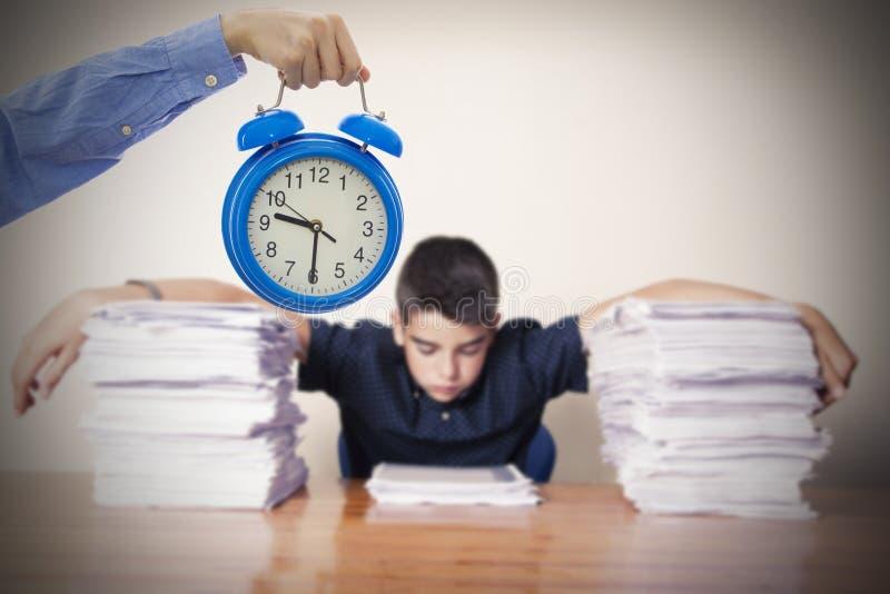 Mano con estudiar del reloj y del niño foto de archivo